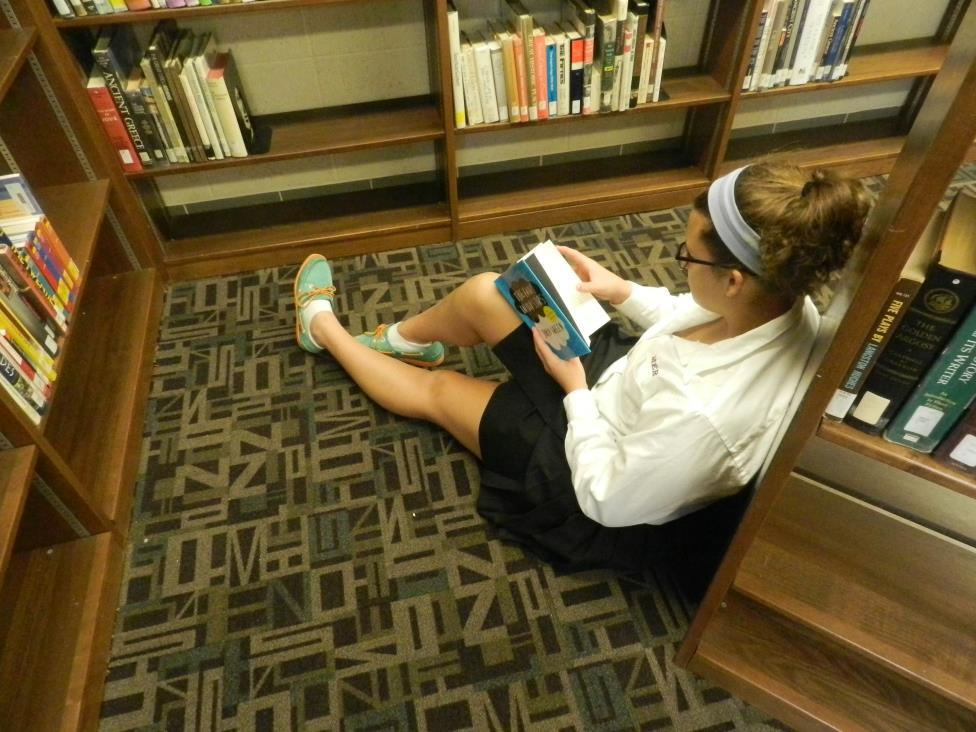 Junior Emily Gates reading The Fault in Our Stars in the Mercy High School media center.