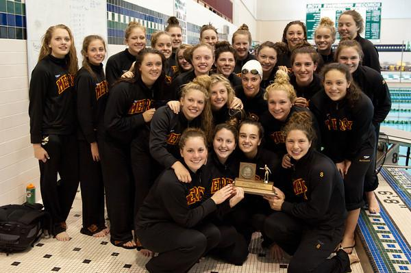 The Mercy swim team poses with their ninth consecutive Oakland County Champion trophy at Lake Orion high school.