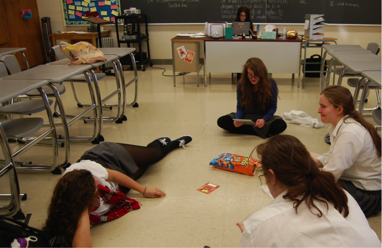Seniors Meaghan Tilson, Amelia Fanelli, Christina Gee, and Alise Wenner convene for a Dead Poets Society Meeting, reading from a Thanksgiving children's book of poems.