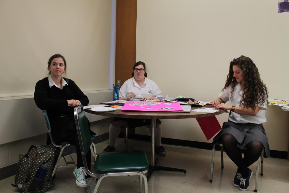 """JCl members (From left) Molly Murphy, Christina Gee and Alise Wenner fill out their bingo charts in hopes of winning a prize, and getting the chance to yell """"Winko""""."""