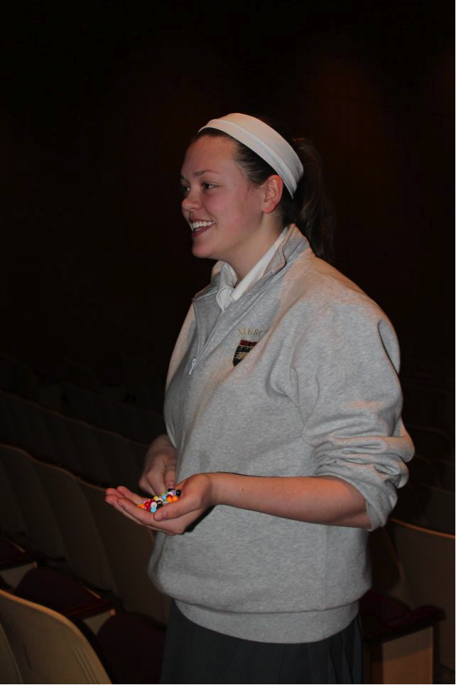 Senior Kelsie Arlin passes beads out to club members to decide small groups.