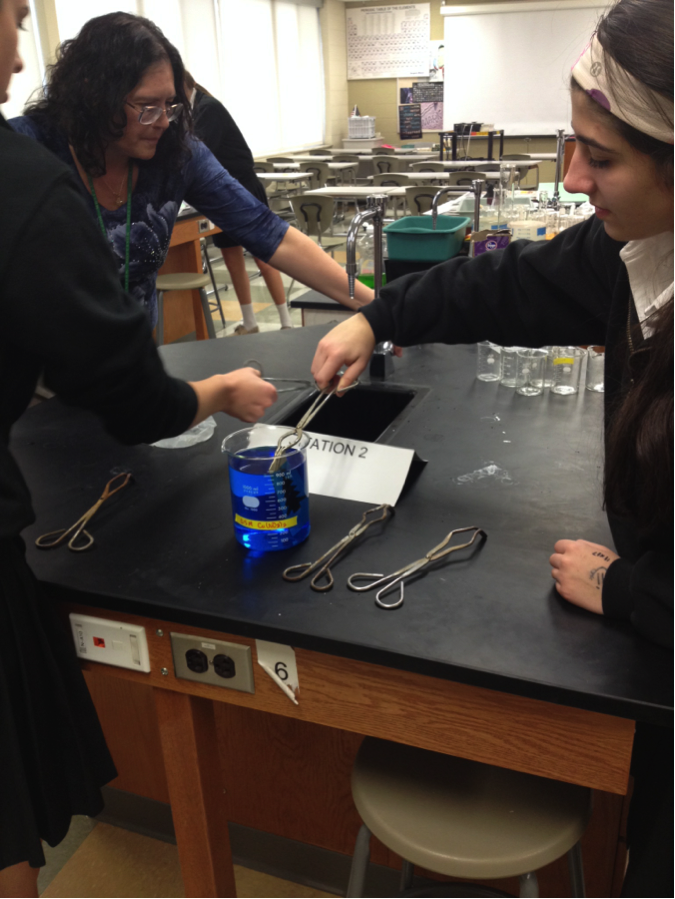 Students dip metal ornaments into chemicals to reveal designs.