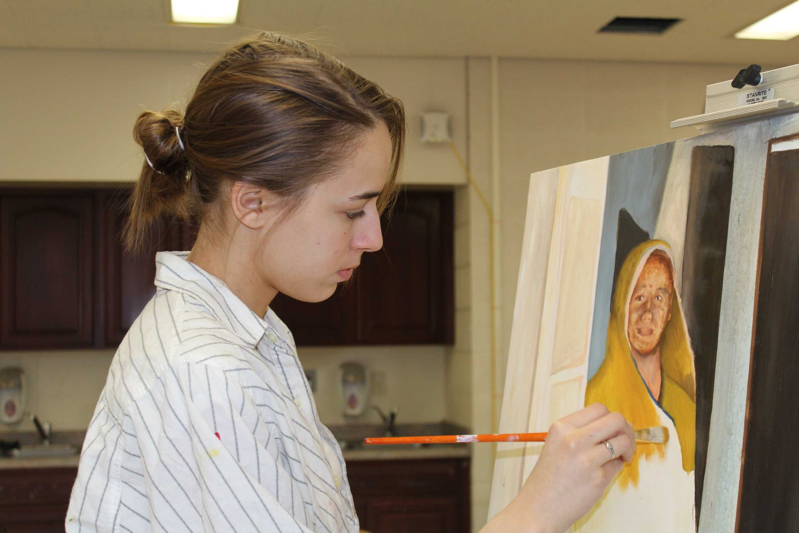 Junior Jaya Jankowski uses a dry brushing technique to block basic shapes into the first of many layers of her piece for Painting 2.  Photo Credit: Alicia Finnorn
